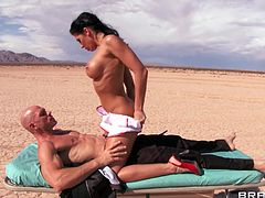 Johnny Sins is in a coma. When milf doctor Rachel Starr comes to check on him her imagines he's fucking her out in the middle of nowhere. He sucks her tits and she gives him a nice two-handed handy in the desert.
