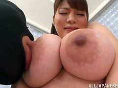Kurumi Kokoro is an amazing Japanese chick with very big tits. Two guys in masks lick her tits and then she gives a titjob to them.
