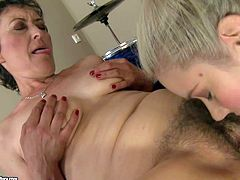 Smoking hot young blonde beauty with pony tail and stunning blue eyes in red fishnet stockings licks short haired brunette granny to orgasm in kinky action filmed in close up