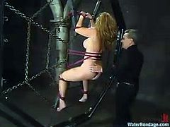 Sexy babe gets tied up. They guy fixes claws to her nipples and spanks her ass. After that the guy trows her in the aquarium and chokes her with rope.