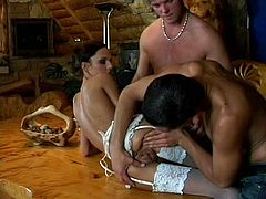 Romanian beauty Amanda is getting fucked on that table by two horny guys. She looks damn fine in that sexy white lingerie and makes the boy's cocks rock solid. She gives one of them a lustful blowjob while looking at us and in that time the other guy eats her pussy. Would some cum look great on her lingerie?