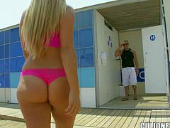 Carol Ferrer is a perfect bodied sexy blonde in pink bikini. Bubble butt doll bares her amazing round tits and gives handjob to lucky dude in public place. Watch her bare her assets at the beachside.