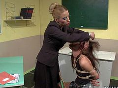 Schoolgirl Betty Stylle gets tied to chair in the middle of the classroom by her teacher Nikky Thorne. Watch long haired sweet brunette in uniform get dominated by crazy blond woman.