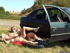 See a vicious mature blonde giving a young stud a car blowjob before he pounds her clam on the grass by the road.