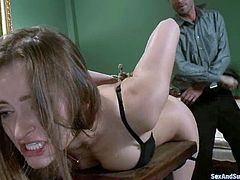 Amazingly hot girl lies on a table being gagged and tied up. The guy comes up from behind and drills her vagina.