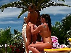 Aleska Diamond and her love partner are tanning on the green terrace and kissing each other. They are almost naked but for the tight thongs that cover the most tasty body parts.