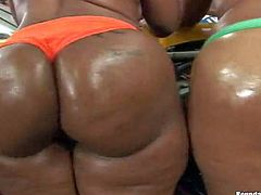 Brown babes Cherokee and Mia with amazing big butts pose topless in a garage before they take off their tight color panties. They show off off their bare booties and natural tits. White guy loves their butts.