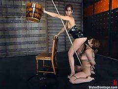 Sexy chick gets gagged and tied up to a chair. After that the other girl turns a jet of water on her pussy. Later on they use a strap-on as well.