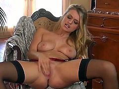 Pretty young blonde slut Natalia Starr is sitting in armchair nude in hot nylon stockings and naughtily masturbating her pussy.