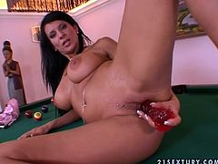 Sexy brunette girl in pink lingerie and high heels poses lying on the billiard table. Then she licks a dildo and starts to shove it in her pussy.