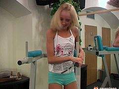 Skinny blond chic takes off her clothes while exercising in gym before demonstrating her tiny pinkish shaved vagina while sitting on fitness machine.