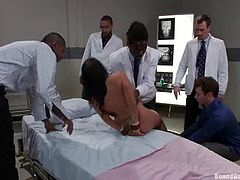 Sizzling dark-haired milf is having fun with a few men indoors. The guys mouth-fuck the bitch and then destroy her hot holes by turns.