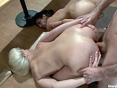 Blonde and brunette chicks fuck each other with strap on in a locker room. After that they get their asses fisted and fucked by a guy.