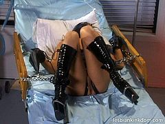 Divine slut in lates mask and lingerie lies on a medical lounge bandaged while an insatiable domina pokes her shaved cunt with a curvy dildo and later sticks it deeply into her mouth in BDSM-involved sex video by Pack of Porn.