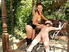 Red-haired sophisticated domina slaps a skinny body of blond hussy that is tied to the cage with her lash in sizzling hot BDSM sex video.