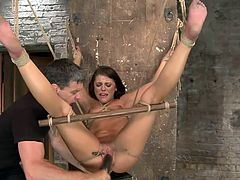 Brunette chick Adriana likes it deep and this guy will make sure she receives what she likes, maybe a bit to much. He tied her up and hanged the bitch, used laundry plies to gape her pussy and now he fucks her roughly with a dildo. Adriana moans as that big dildo stretches her cunt and he fills her mouth with it too