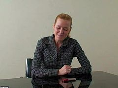 Cute and shy looking blonde babe in dark shirt gives an interview at the desk before her first porn audition and showing all of her talents to the cam