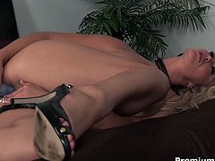 Bootylicious blond milf with oversized milky tits finger fucks her soaking snatch before she lies on the floor with legs spread aside to poke her vagina with a dildo.