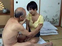 Hot chick gets her tits licked by an old man. After that she strips her clothes off and lies down on the floor. Then she gets fucked in different positions.