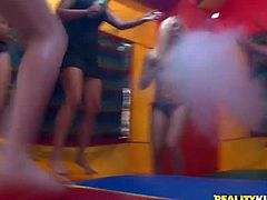 Hot and handsome babes enjoy in putting on their bikinis and jumping in an inflatable bouncing castle in front of the cameras and having fun while showing their boobs