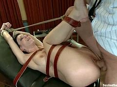 Horny brunette chick lies on a medical chair being tied up. Later on she gets her pussy toyed and ass fucked.