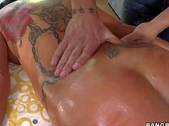 Busty and pretty hot brunette pornstar with huge melons and tattooed back Sienna West enjoys in getting really arousing massage session on the table by her masseur and enjoys