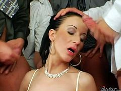 Horn made brunette mature in seductive white lingerie and stockings gives a blowjob while getting boffed in doggy pose surrounded by aroused dudes that jerk off looking at her before she stands on her knees to welcome numerous shots of hot sperm in sizzling hot gangbang sex video by Tainster.