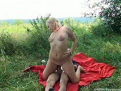Slutty blond milf gives a mouth fuck to aroused daddy while lying on the blanket outdoors before she rides him in reverse cowgirl style in sultry sex video by Pack of Porn.