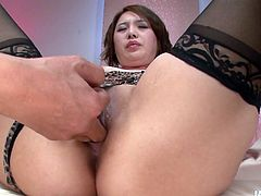 Lustful Japanese bitch in flirty leopard-printed lingerie and seductive black stockings lies on her back with legs spread aside while insatiable dude tickles her cunt with vibrator.