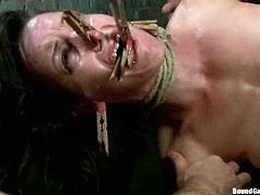 Brunette girl gets tied up, blindfolded and gagged. After that guys fix clothespins to her face and tongue. Then she gets double penetrated.