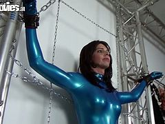 Naughty girls are playing frisky sex games. Brunette one is standing along the wall being crucified. She is wearing blue color latex costume that is hugging her body tight. Brunette slut is getting tormented by her lover. The latter uses long dildo in kinky sex games. Dude, just check out this video, you gonna luv it.