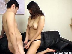 Sweet Japanese woman in Black lingerie lies down on a sofa and touches a dick. After that she also sucks it with pleasure.