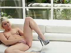 Smooth glamour babe Ash Hollywood is sitting on the couch by the window and passionately fondling he