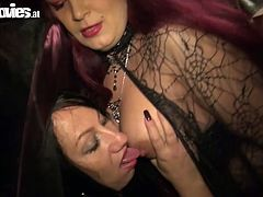 Kinky bitches wearing Halloween costumes are pleasing one another at the party. Redhead one suckles firm nipples looking straight to the cam.