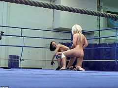 Liz and her lusty lesbian friend enjoy in fighting on the floor in the gym and have a hot nude wrestling session in front of the camera crew and have fun