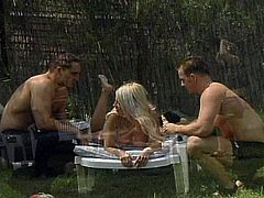 See two horny studs banging each other and a sexy blonde during a vicious backyard bisexual threesome.