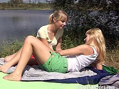 Two slender blondies are on the river bank. Ardent chicks with nice tits and smooth asses don't care about sunbathing. As both gals are horny, they take off shorts and tops to tease each other's already wet pussies for orgasm.
