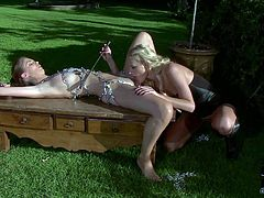 Long haired stunning blonde with tight ass and pretty face in sexy black dress dominates over nude chained slave in arousing bondage action in backyard while neighbor films them