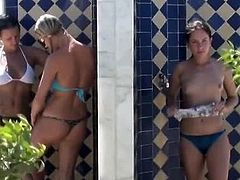 Three amateur girls in swim suits taking a shower at the beach