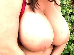 Full figured biker chick Kora with long red nails and huge jaw dropping tits in leather outfit and red underwear slowly strips while teasing in arousing solo action in backyard.