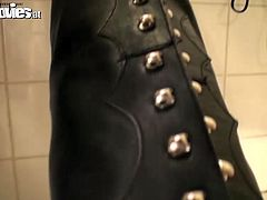 She tall brunette model with long legs and skinny white ass. She strips in the bathroom to put on dirty leather costume. Her slave helps her put on long leather jackboots.