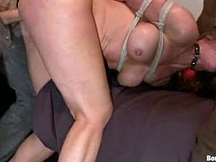 Tied up Danny Wylde stands on her knees sucking big hard cocks. After that she gets double penetrated in a rough manner on a bed.