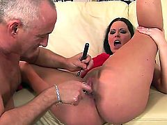 Beautiful brunette bitch Simony Diamond is lying on the couch with pulled up and bent in knees legs and being pleased with dildo toys by her bald boyfriend.