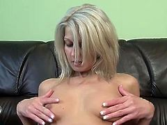 Kelly Wells teases her nipples with her legs spread and then she lies on the sofa naked and rubs her slit.