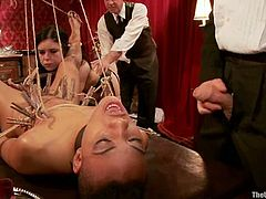 Black girl lies on a table in the middle of the room. Some people tie her up and fix clothespins to her body. Later on two bonded chicks get fucked deep and hard.