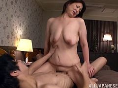 Mature Japanese woman undresses and gets her pussy fingered by younger guys. After that she sucks a cock and gets fucked doggystyle at the same time.