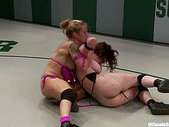 Two chicks in bikinis fight in the ring and this battle turns to a wild lesbian sex. They toy each others pussies with a vibrator and a strap-on.