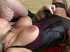 Slutty aunty is wearing sassy corset and fishnet stockings. She is sitting on a stool spreading her legs wide. Two perverted dudes join her on set finger fucking her hard while her hands and legs are hogtied to the chair. Watch this kinky porn video with restraint elements.