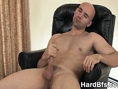 Good looking bald man sits on the comfy leather chair and plays with his white dick, sliding his hand up and down to work his magic.