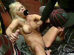This petite blond siren is so fucking horny! She gets naked and starts sucking two thick dicks in the dressing room. Public perversions!